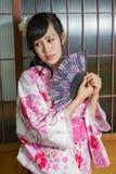 Asian woman in kimono holding fan stock photos