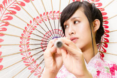 Asian woman in kimono holding umbrella Stock Image