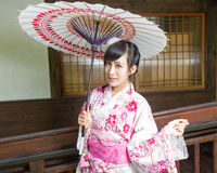 Asian woman in kimono holding umbrella. Asian woman wearing a kimono in front of  Japanese house holding umbrella Stock Images