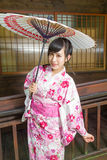 Asian woman in kimono holding umbrella. Asian woman wearing a kimono in front of  Japanese house holding umbrella Royalty Free Stock Photography