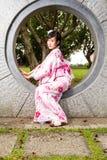 Asian woman in kimono sitting in wall Stock Image