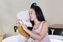 Asian woman kissing her dog on the bed Stock Images