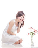 Asian woman kneeling and looking at flowers Royalty Free Stock Photography
