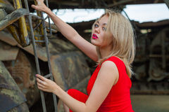 Asian woman on ladder. Young blond haired asian woman in red dress climbing ladder on heavy equipment Stock Photo