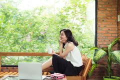 Asian woman with laptop sitting near window in creative office o Royalty Free Stock Image