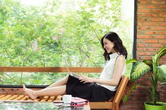 Asian woman with laptop sitting near window in creative office o Stock Images