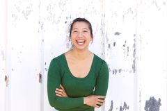 Asian woman laughing against white wall Stock Photo