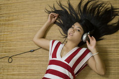 Asian woman laying down listening to music Stock Photo