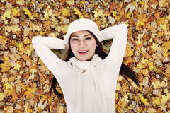 Asian woman laying happily on autumn leaves Stock Images