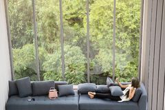 Asian woman laying on sofa near big glass wondows, relaxing alone in house with green forest in background stock photos