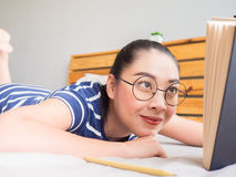 Woman lie on bed and read book. Asian woman lie down on bed and reading book Stock Photography