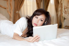 Asian woman holding a tablet lying on her bed Stock Photography