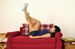Asian woman lies on red sofa legs up Stock Images
