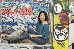 Asian Woman in lifestyle locations by Public Grafitti Wall Stock Images