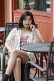 Asian Woman in lifestyle locations sitting at a table on the street Stock Image