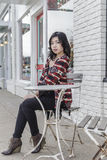 Asian Woman in lifestyle locations sitting at a table on the street Stock Images