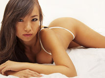 Asian woman in lingerie lying on bed. Royalty Free Stock Photo