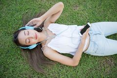 Asian woman listen music on grass Stock Images