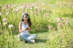 Asian woman listen music in summer garden. Portrait of Happy beautiful Asian woman listen music by earphone and sit on grass field with flowers in morning Stock Photos