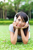 Asian woman listen to song lying on grass Royalty Free Stock Photo