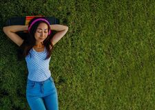 Asian Woman Listening To Music With Headphones And Laying On A Grass Field