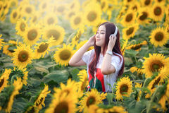 Asian woman listening to music in the sunflower field happily. Stock Images