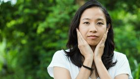 Asian woman long hair with facial epression green nature backgro Royalty Free Stock Photography