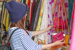 Asian woman looking at bags on rack Stock Images