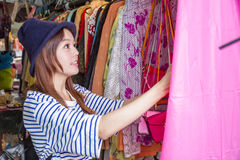 Asian woman looking at clothes on rack Stock Photography