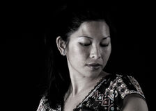 Asian woman looking down. On black background Stock Photography
