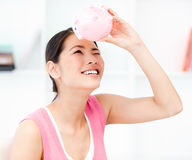 Asian woman looking through an empty piggy bank Stock Photo