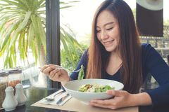 An Asian woman looking and enjoy eating Ceasar salad in restaurant royalty free stock image