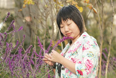 Asian woman looking at flowers Royalty Free Stock Images
