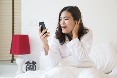 Asian woman looking at her phone with an surprised expression on her face Stock Photography