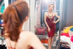 Asian woman looking mirror shopping choosing Stock Image