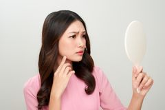 Asian woman looking at the mirror with the trouble on her skin. Asian woman looking at the mirror with the trouble on her skin Stock Photo