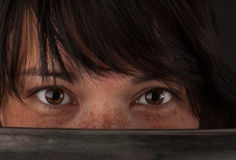 Asian woman looking over the blade of her sword Stock Photography