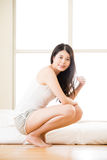 Asian woman looking radiant wake up in early morning light. Asian woman looking radiant wake up in the early morning light, bedroom background royalty free stock photo