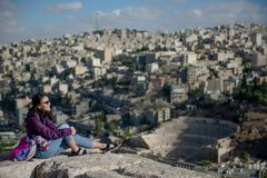 Asian woman looking at view of Amman city, Jordan. Young Asian woman tourist sitting on the rock enjoy looking at the view of Amman city from Citadel viewpoint royalty free stock images