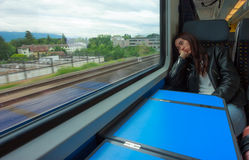 Asian woman looks outside of the train`s window, looking bored or tired of traveling too long.  Stock Image