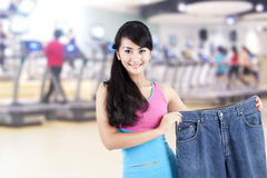 Asian woman loosing weight posing in gym Royalty Free Stock Photo