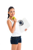 Asian woman losing weight with diet. Young Asian woman losing weight by living healthy and eating fruits Royalty Free Stock Image