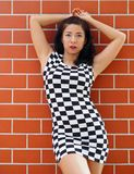 Asian woman lying against a brick wall Royalty Free Stock Image