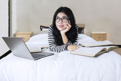 Asian woman lying on bed with laptop and books. Portrait of attractive woman lying on bed with laptop and books while looking at copyspace Stock Images