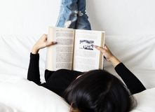 Asian woman lying on bed reading book Royalty Free Stock Photography