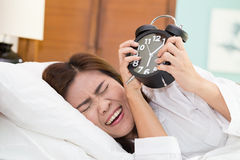 Asian woman lying in bed suffering from alarm clock sound. Not e Stock Photo