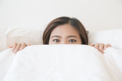 Asian woman lying in bed under blanket Stock Images
