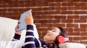 Asian woman lying on the couch listening to music Stock Photos