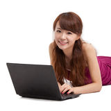 Asian woman lying down with laptop Stock Image