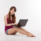 Asian woman lying down with laptop. Royalty Free Stock Image